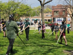 Picture of longsword students learning a low guard outside in the park