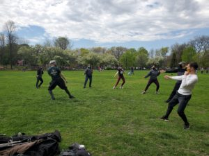Students practicing their lunge outside in a park